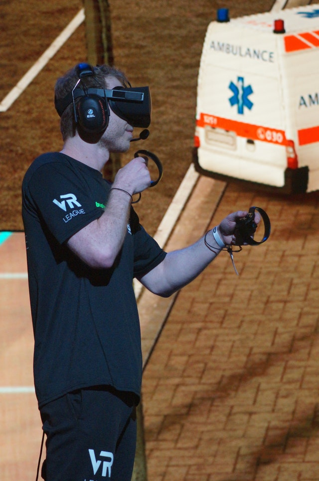 a man holding two motion controllers