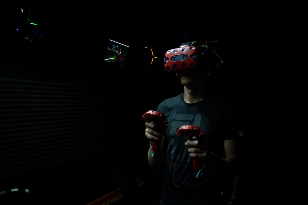 a young man holding motion controllers and wearing VR headset